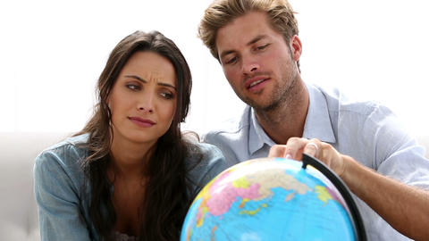 Couple looking at globe and picking travel destination Live Action