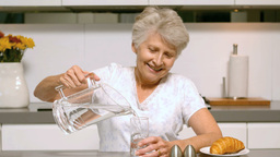 Retired Woman Pouring A Glass Of Water For Breakfa stock footage