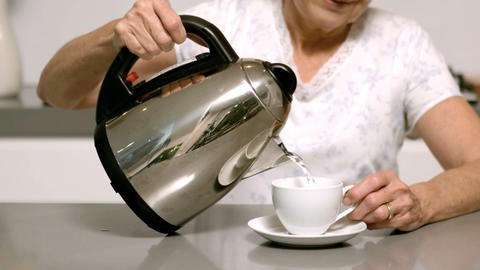Woman pouring boiling water from kettle into cup Footage