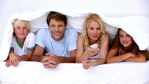 Family lying under the covers watching tv Footage