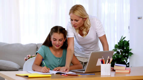 Mother helping her daughter with homework Footage