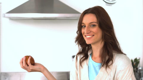 Attractive brunette throwing and catching an apple Footage