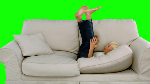 Young boy jumping on the sofa on green screen Footage