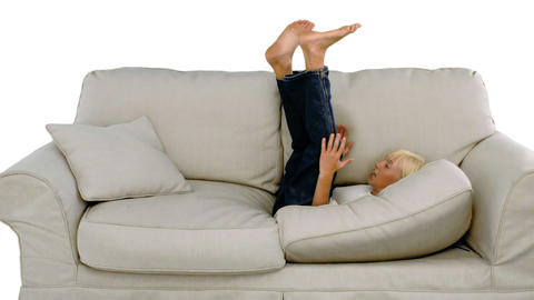 Young boy jumping on the sofa on white background Footage