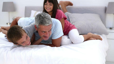 Father and his children playing on the bed Footage