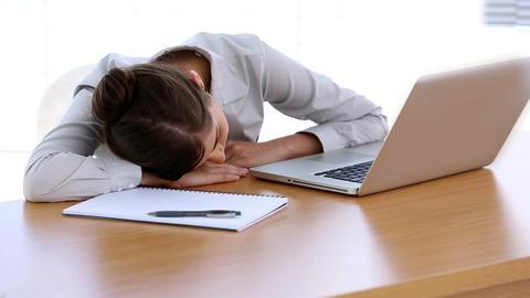 Businesswoman asleep on her desk Live Action
