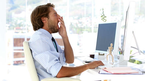 Businessman yawning at his desk Footage