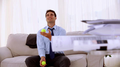 Happy businessman juggling with tennis ball Footage