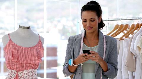 Pretty fashion designer texting in her studio Footage