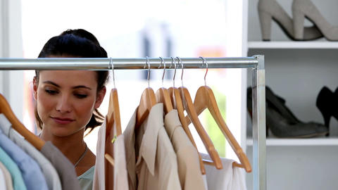 Beautiful woman picking clothes on a clothes rail Live Action