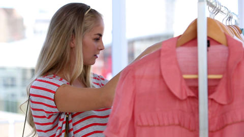 Attractive woman doing shopping in clothes shop Footage