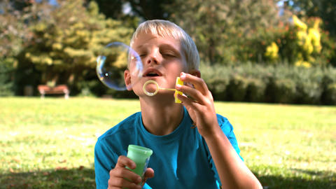Young boy blowing into a bubble wand Footage