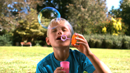 Cheerful young boy blowing into a bubble wand Footage