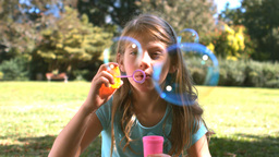 Cute young girl blowing into a bubble wand Footage
