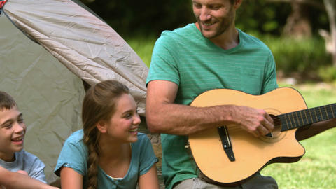 Father playing guitar for his family Footage