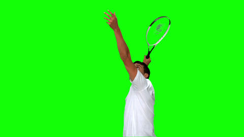 Man serving while playing tennis on green screen Footage