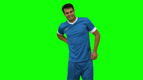 Football player suffering from back pain on green screen Live Action