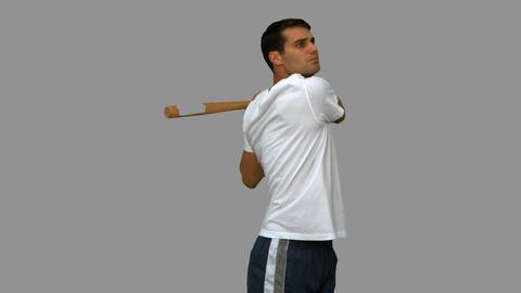 Handsome man playing baseball on grey screen Footage