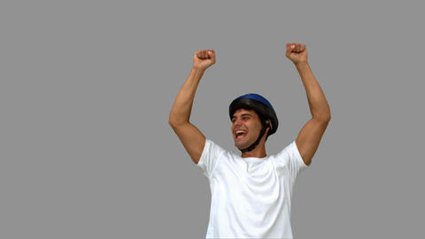Man on his bicycle raising arms on grey screen Live Action