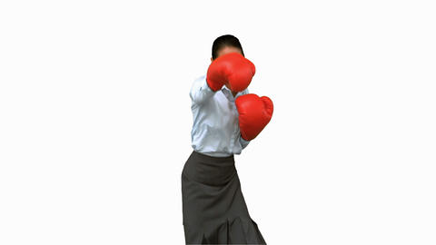 Businesswoman wearing boxing gloves and hitting on white screen Footage