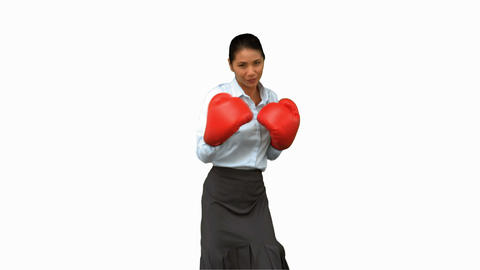 Businesswoman with boxing gloves hitting on white screen Footage