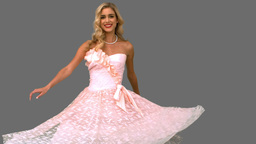 Pretty woman wearing a gown revolving on grey screen Footage