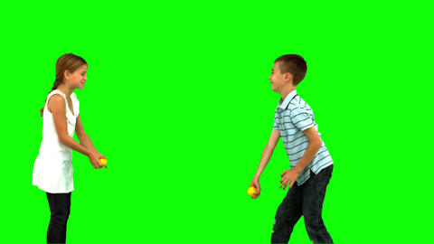 Siblings playing with tennis balls on green screen Footage