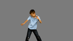 Little boy dancing on grey screen Footage