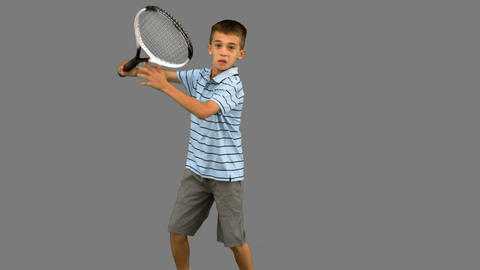 Little boy playing tennis on grey screen Footage