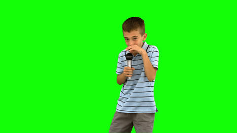 Little boy holding a microphone and singing on gre Footage