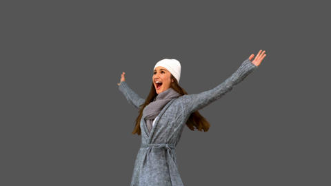 Cheerful young model in winter clothes cheering Live Action
