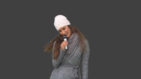 Cheerful young model in winter clothes singing Footage
