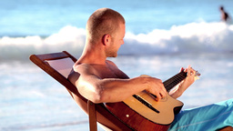 Man playing guitar on the beach Footage