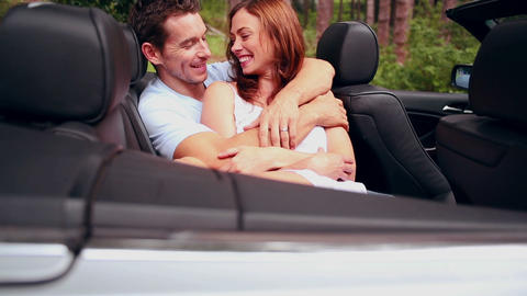 Young couple embracing in a convertible car Footage
