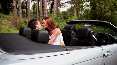 Woman kissing her boyfriend in a convertible car Footage