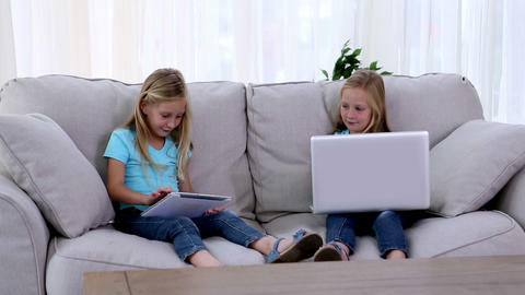 Sisters using laptop and tablet pc Footage