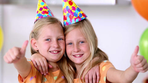 Twin sisters with thumbs up at birthday party Footage