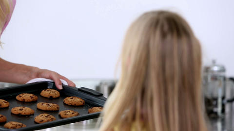 Mother offering hot cookies to her daughters Footage