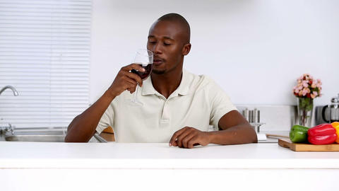 Man tasting red wine in a kitchen Footage