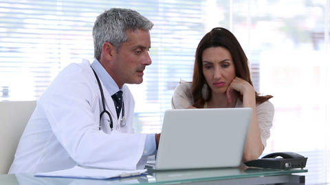 Doctor explaining a patient disease with a laptop Footage