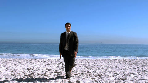 Businessman walking on the beach like a robot Footage