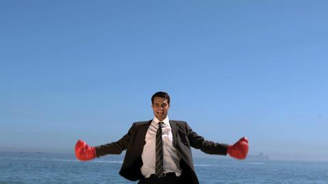 Businessman on the beach raising arms Live Action