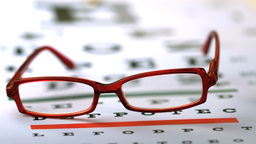 Red reading glasses falling on eye test Footage