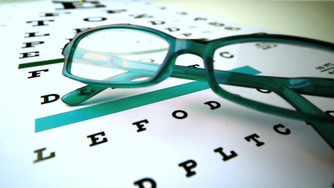 Green reading glasses falling onto eye test Footage
