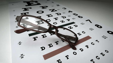 Black glasses falling onto eye test Footage