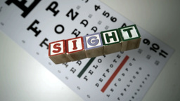 Blocks spelling sight falling on eye test Footage