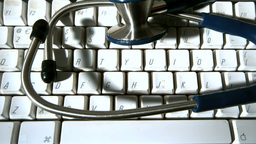 Stethoscope falling onto computer keyboard and then vibrating Live Action
