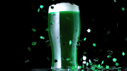 Shamrock confetti next to a pint of green beer Filmmaterial