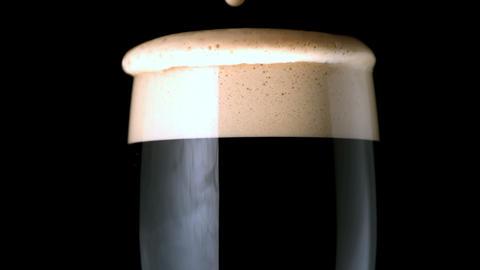 Foam head settling on pint of stout on black backg Footage