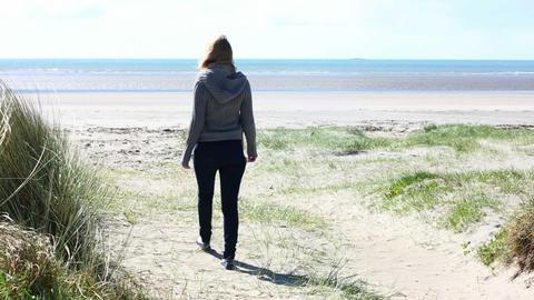 Woman walking on a beach in windy weather Footage